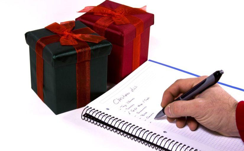Mand der skriver sine gaveønsker ned på papir
