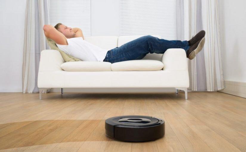 Mand der slapper af i sofaen, mens robotten støvsuger for ham